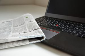 A newspaper next to a laptop